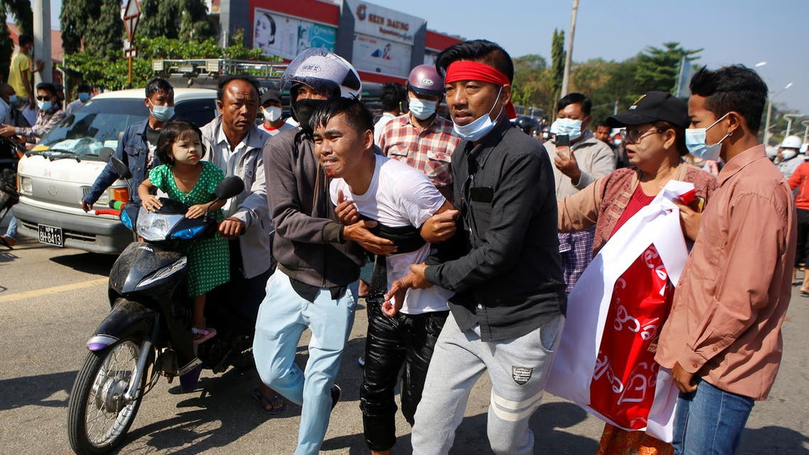 An injured protester is helped by his fellow protesters, at a rally against the military coup and to demand the release of elected leader Aung San Suu Kyi, in Naypyitaw, Myanmar, February 9, 2021. (Reuters)