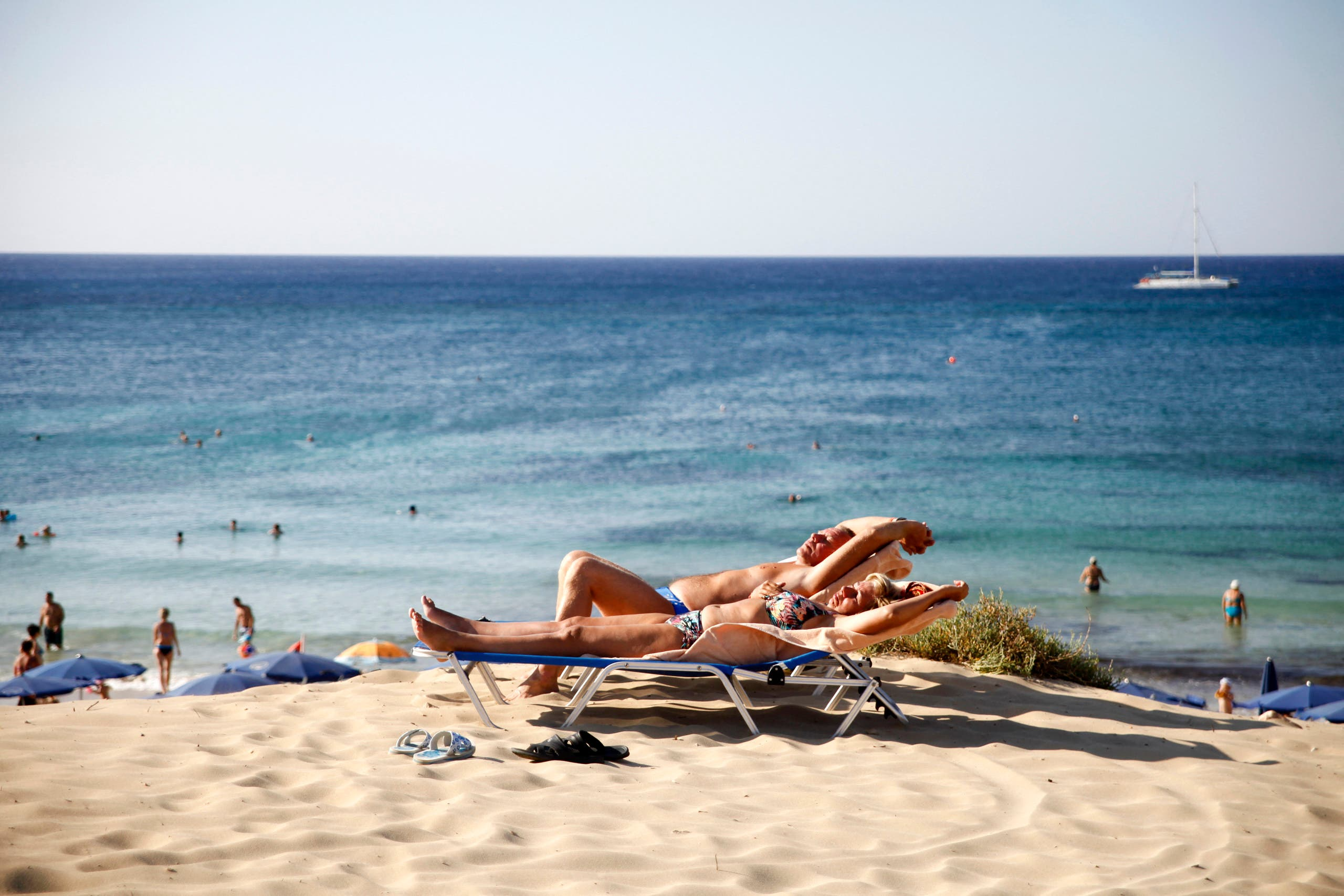 Tourists sunbathe at the beach in the resort town of Ayia Napa in southeastern Cyprus. (File photo: AFP)