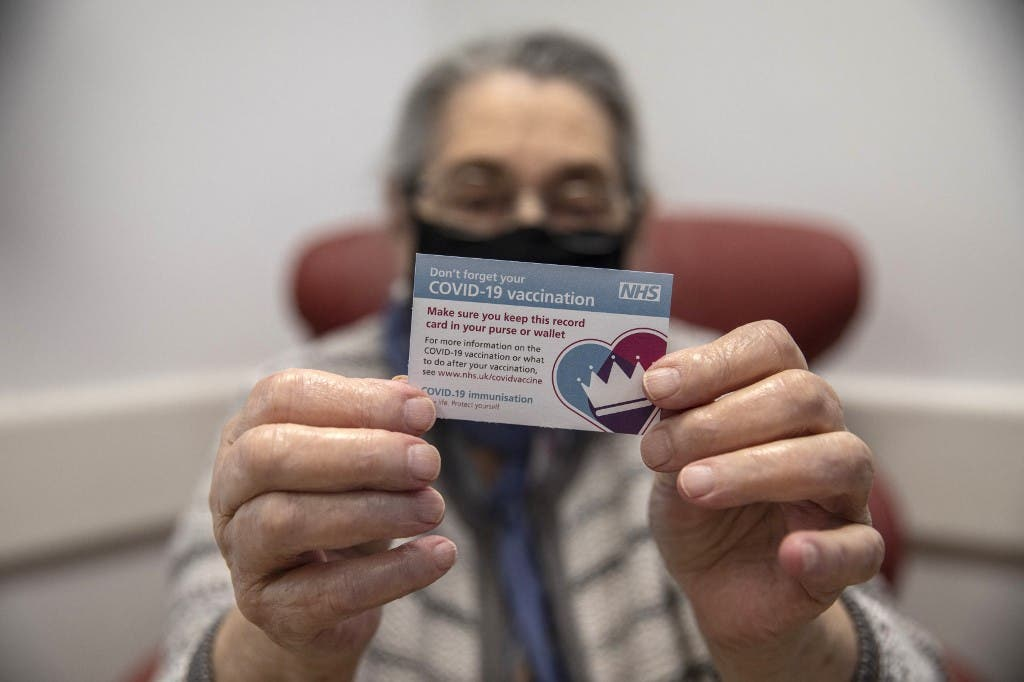 Bernice Wainer, 82, holds up her vaccination card as she receives a dose of the Pfizer-BioNTech Covid-19 vaccine at the Royal Free hospital in London on December 8, 2020 at the start of the UK's biggest ever vaccination programme. (File photo: AFP)