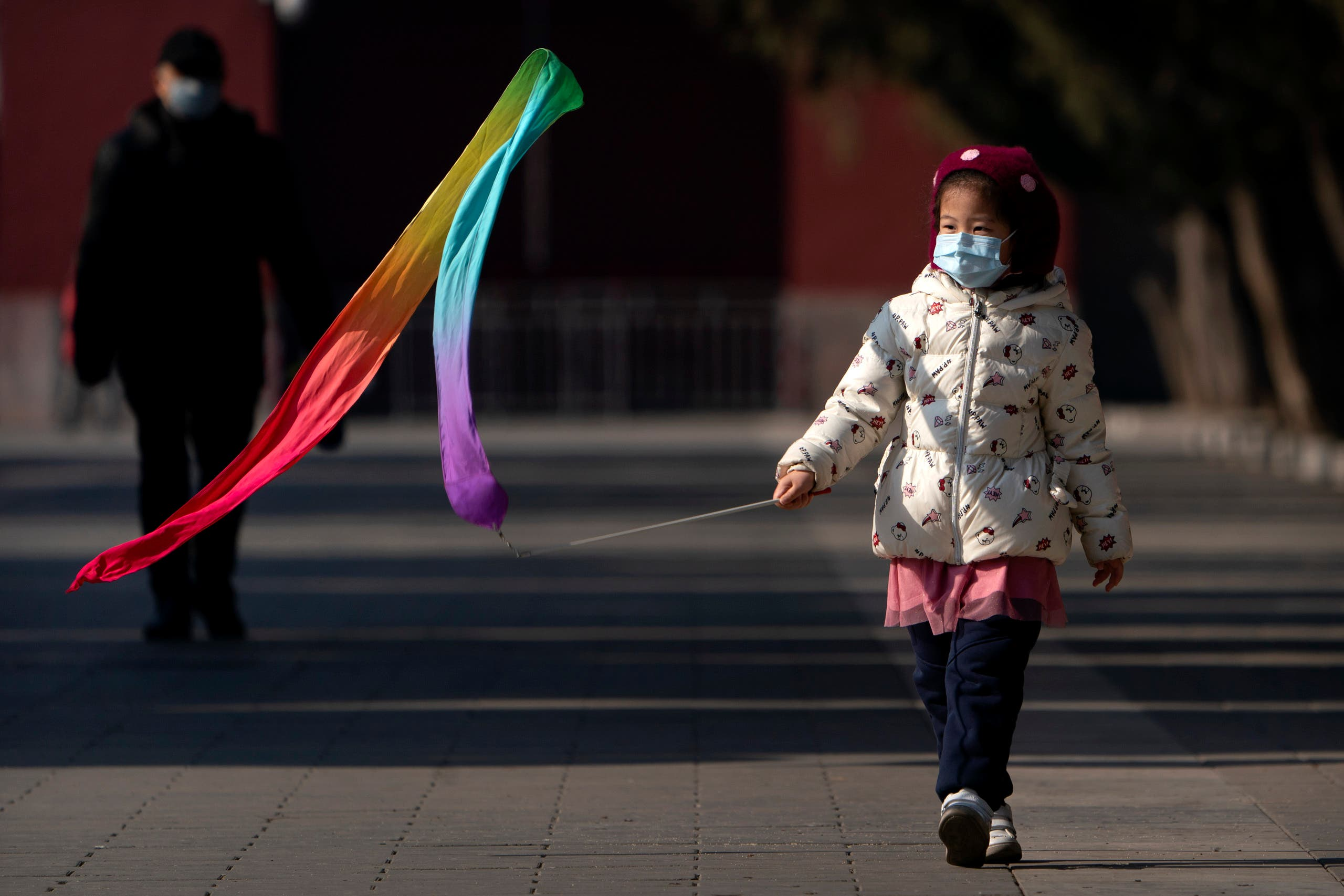 A girl wearing a face mask to protect against the spread of the coronavirus plays with a toy at Ditan Park in Beijing, Tuesday, Feb. 9, 2021. (AP)
