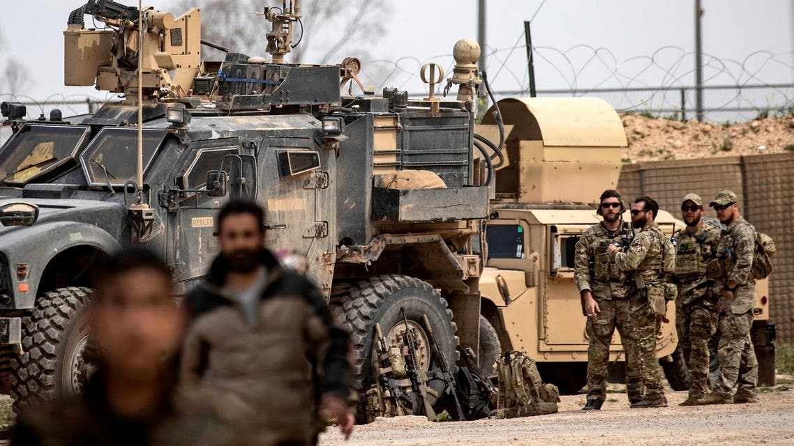 US soldiers gather around their military vehicles near Omar oil field in the eastern Syrian Deir Ezzor province on March 23, 2019, after US-backed Syrian Democratic Forces (SDF) announced the total elimination of the Islamic State (IS) group's last bastion in eastern Syria. Kurdish-led forces pronounced the death of the Islamic State group's nearly five-year-old caliphate early on March 23 after flushing out diehard jihadists from their very last bastion in eastern Syria. In Al-Omar, an oil field used as the main SDF staging base for the final phase of the assault, fighters in their best fatigues laid down their weapons and broke into song and dance.