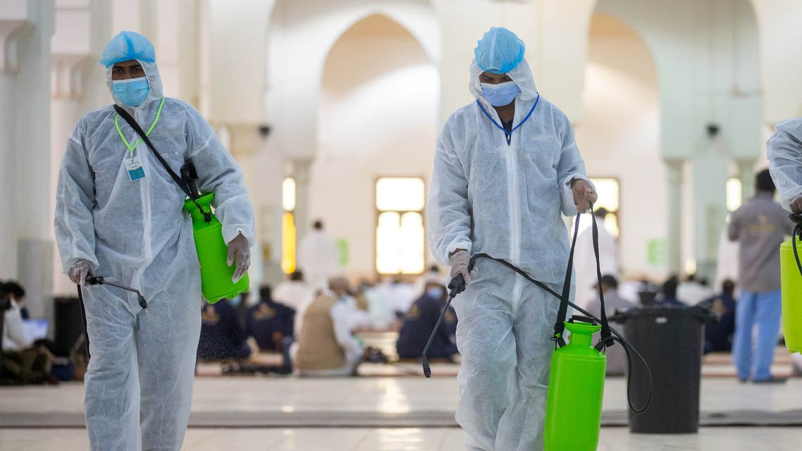 Health workers wearing personal protective equipment (PPE) disinfect the floor as Muslim pilgrims pray inside Namira Mosque in Arafat amid the coronavirus disease (COVID-19) pandemic, outside the holy city of Mecca, Saudi Arabia July 30, 2020. (Reuters)