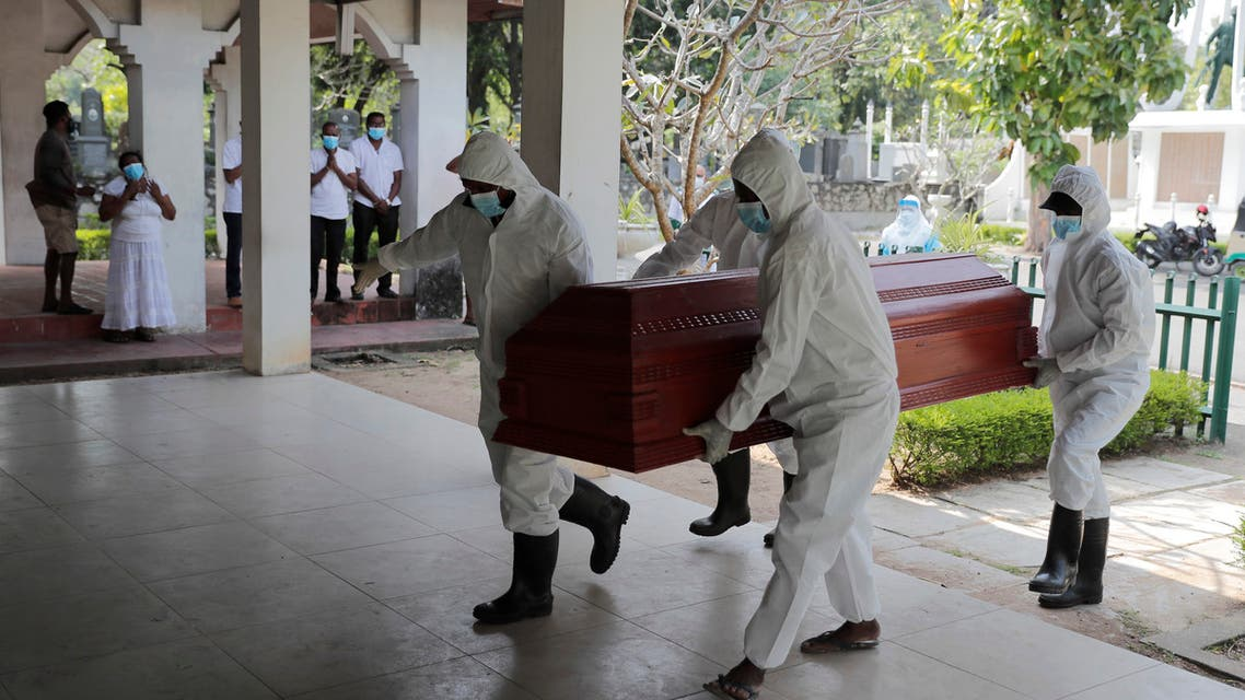 Sri Lankan health workers carry a coffin carrying remains of a COVID -19 victim to a cremation furnace as relatives watch from a distance in Colombo, Sri Lanka, Wednesday, Feb. 10, 2021. (AP)