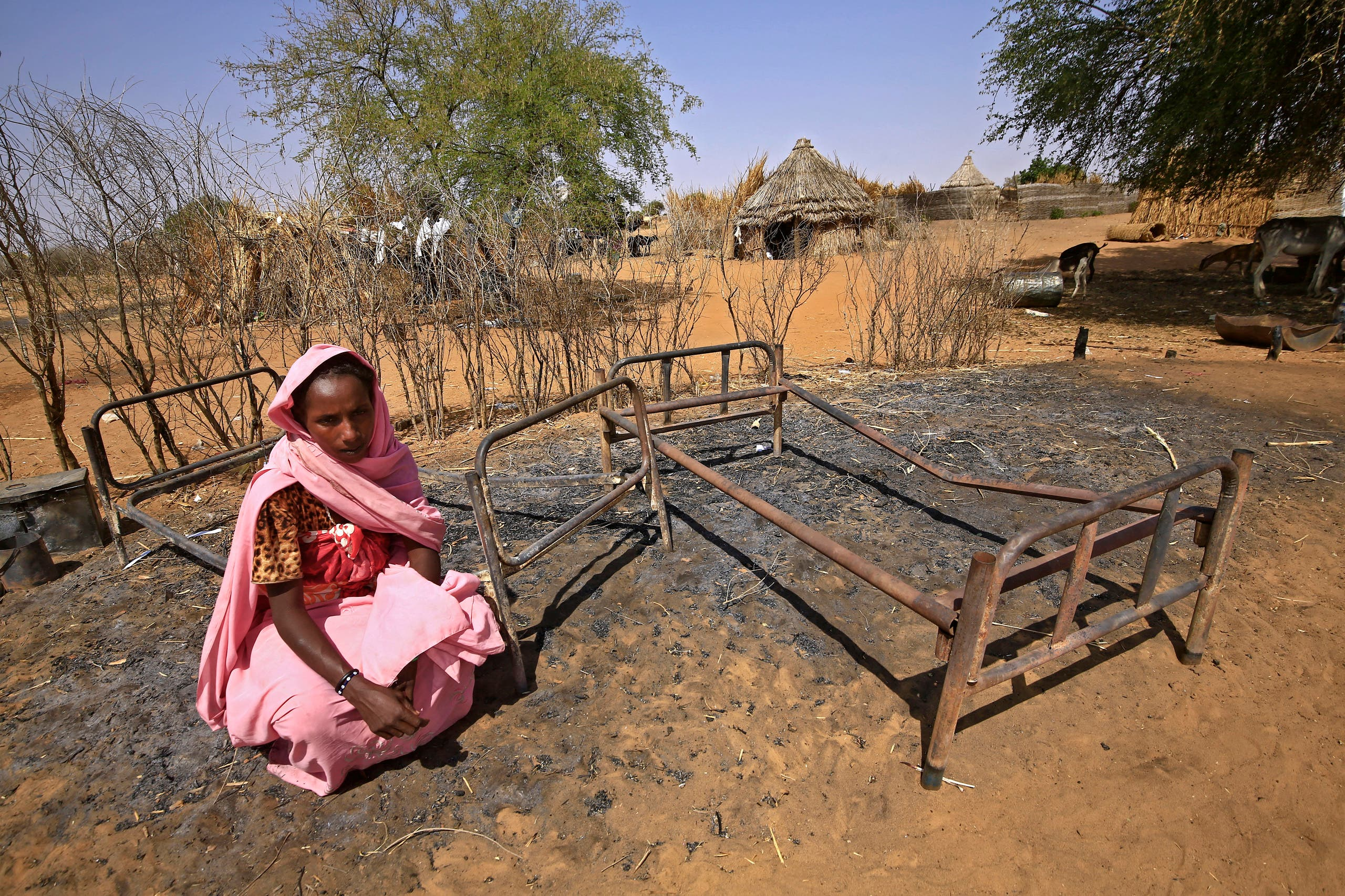A Sudanese woman is pictured next to burnt beds following violence in the village of al-Twail Saadoun, 85 kilometres south of Nyala town, the capital of South Darfur, on February 2, 2021. (AFP)
