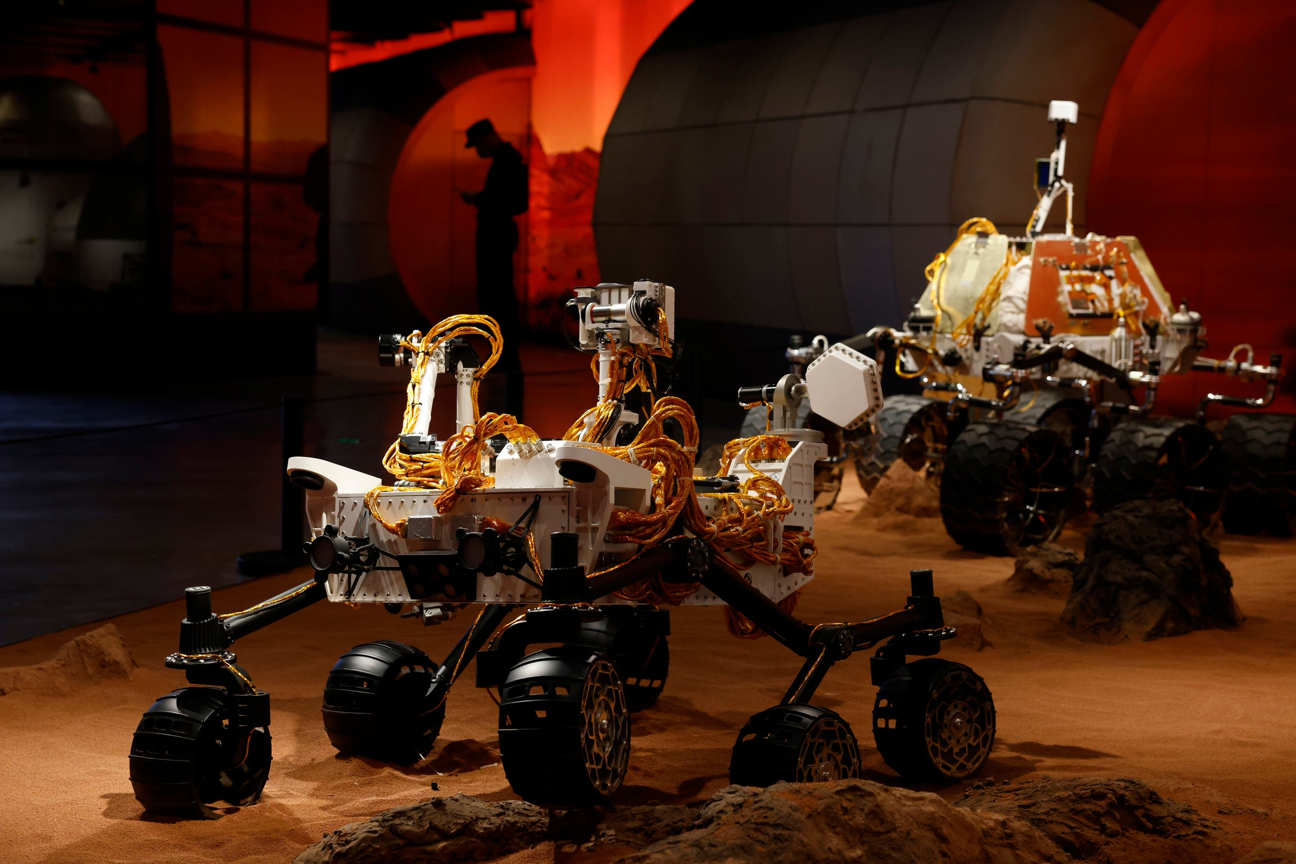 A security guard is silhouetted near a display depicting rovers on Mars during an exhibition in Beijing on Thursday, July 23, 2020. (AP Photo/Ng Han Guan)