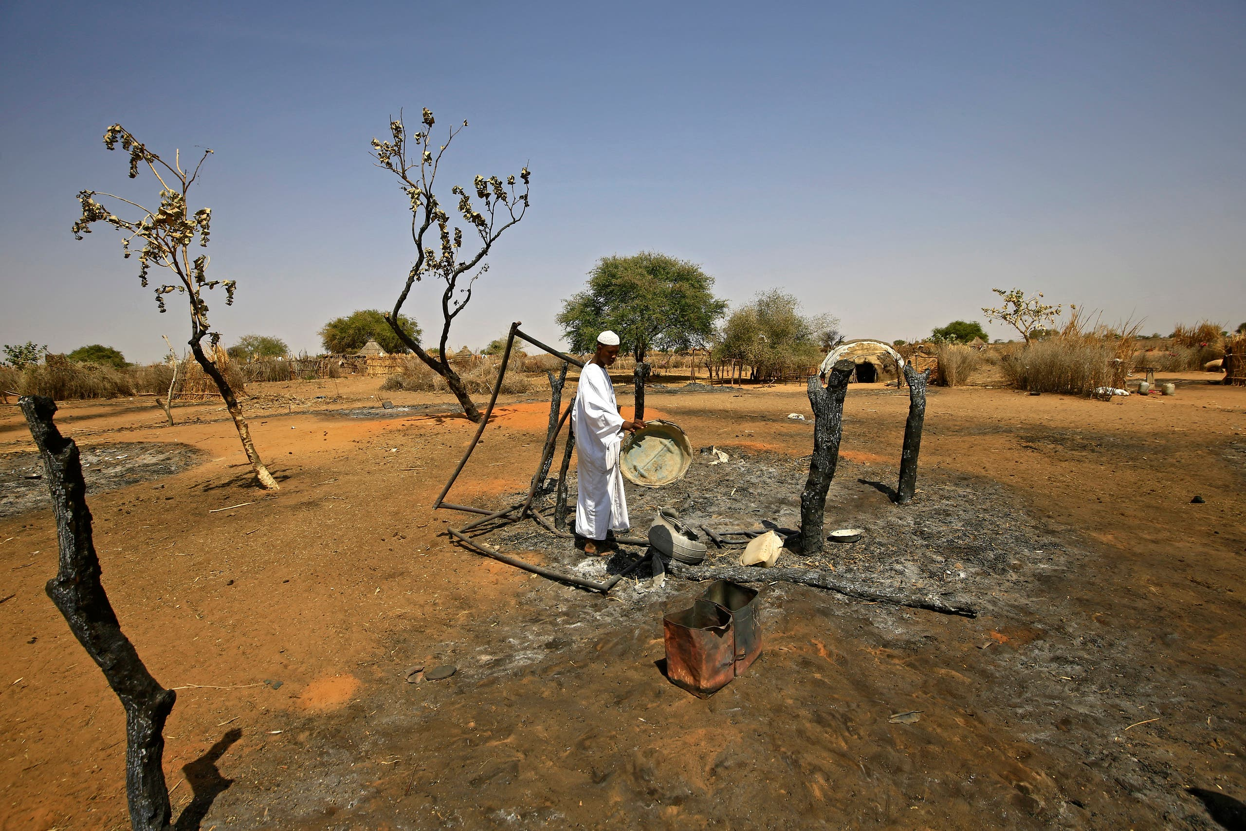 A Sudanese man checks the aftermath of violence in the village of Twail Saadoun, 85 kilometres south of Nyala town, the capital of South Darfur, on February 2, 2021. (AFP)