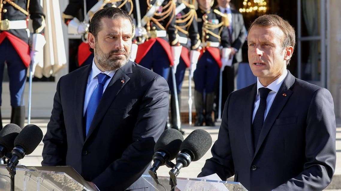 French President Emmanuel Macron (R) is watched by Lebanese Prime Minister Saad Hariri in Paris on Sept. 20, 2019. (AFP)