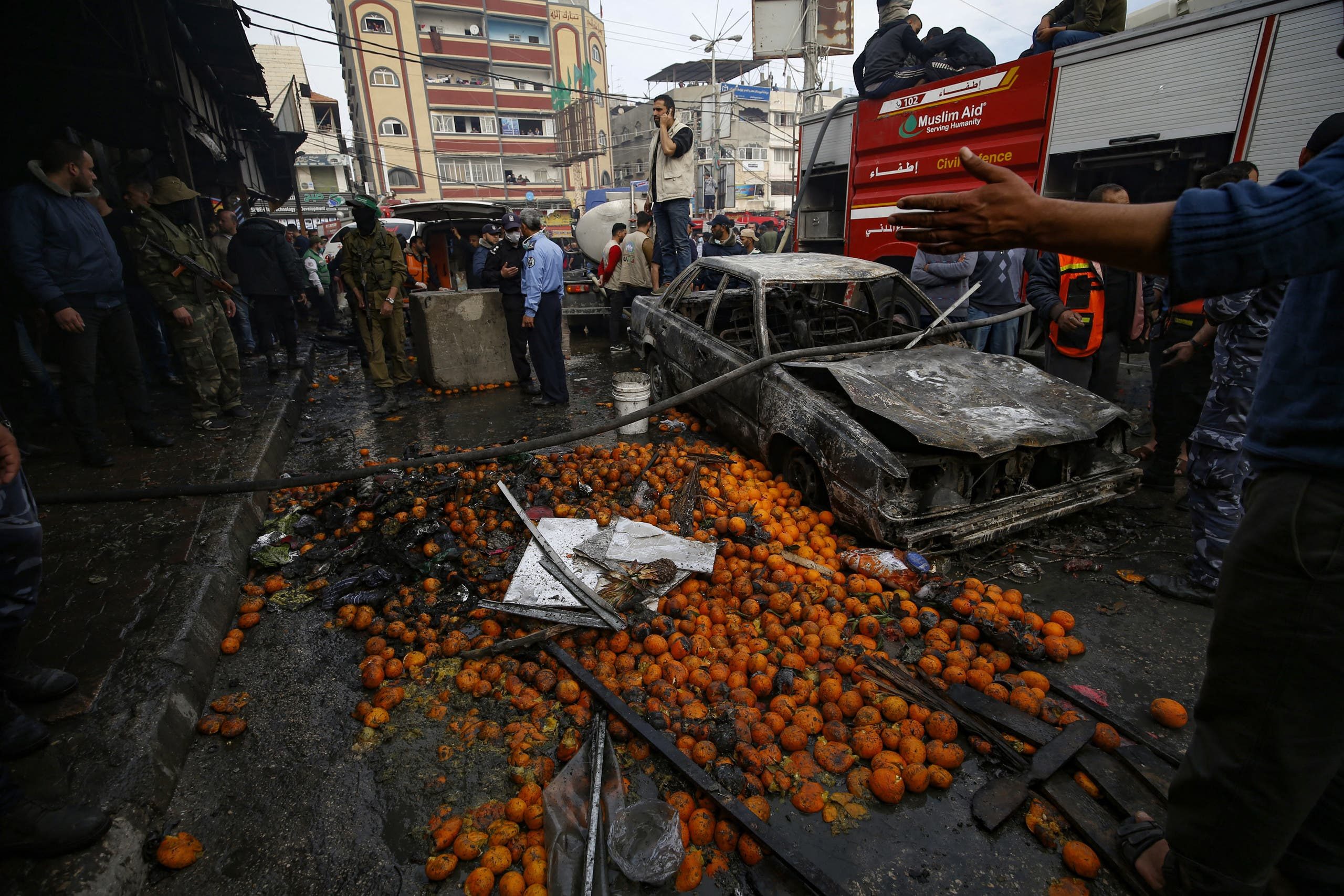 Fruit is scattered across the street near a charred car after a fire that broke out in a market in the refugee camp of Nuseirat in central Gaza Strip, on March 5, 2020. (AFP)