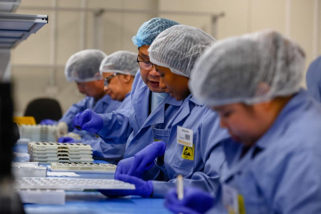 Employees work on the production line of a coronavirus home test unit in Brisbane. (AFP)