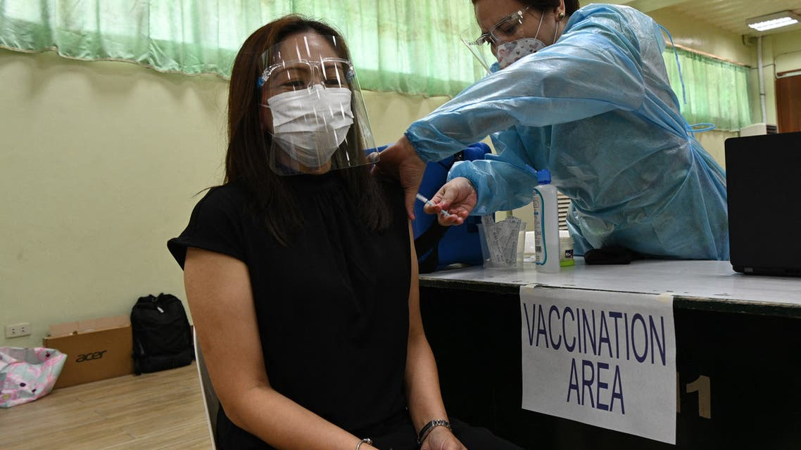 A city hall employee (L) takes part in a vaccination simulation in Manila. (AFP)