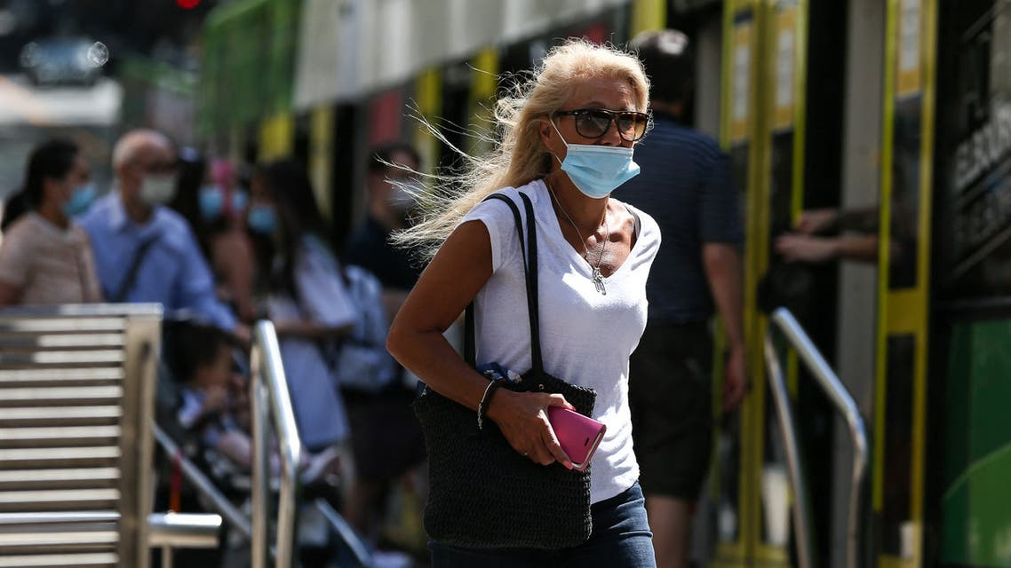 A woman wearing a face mask walks on a street in Melbourne on February 12, 2021, after authorities ordered a five-day state-wide lockdown starting at midnight local time to stamp out a new coronavirus outbreak. (AFP)