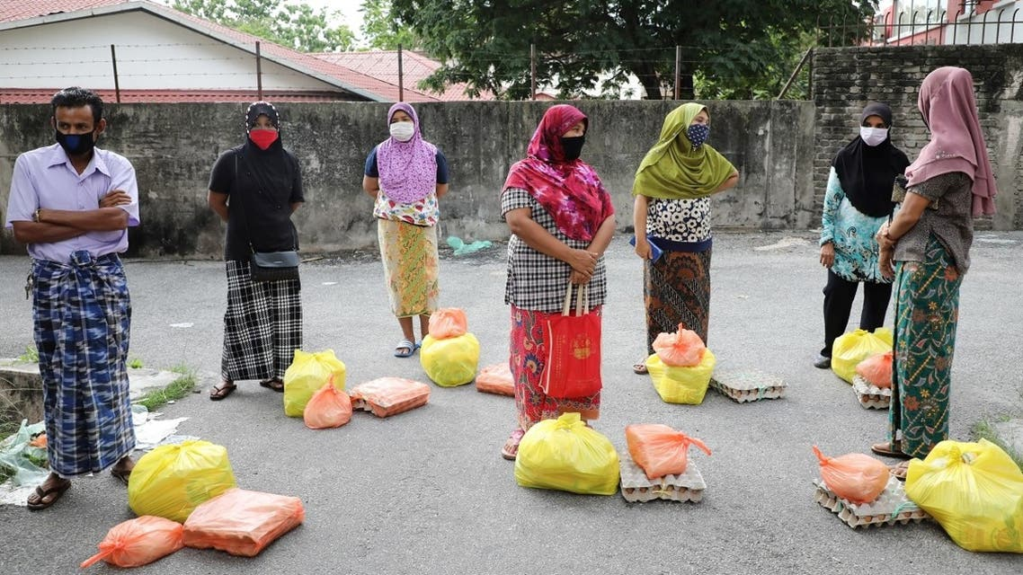 Rohingya refugees wearing protective masks waiting to receive goods from volunteers, during the movement control order due to the outbreak of the coronavirus, in Kuala Lumpur, Malaysia. (Reuters)