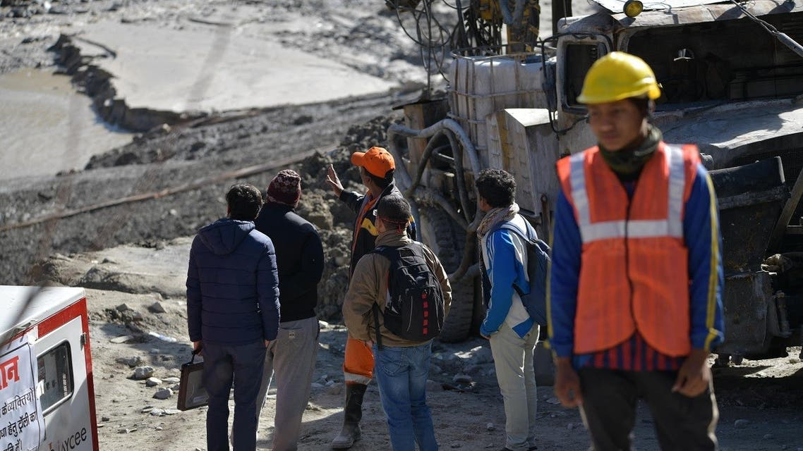Defence research and development organization (DRDO) scientists talk with an emergency and rescue official (in orange cap) after arriving near Tapovan tunnel, where dozens are still feared to be trapped, during rescue operations in Tapovan of Chamoli district on February 12, 2021 following a flash flood thought to have been caused when a glacier burst on February 7. (AFP)