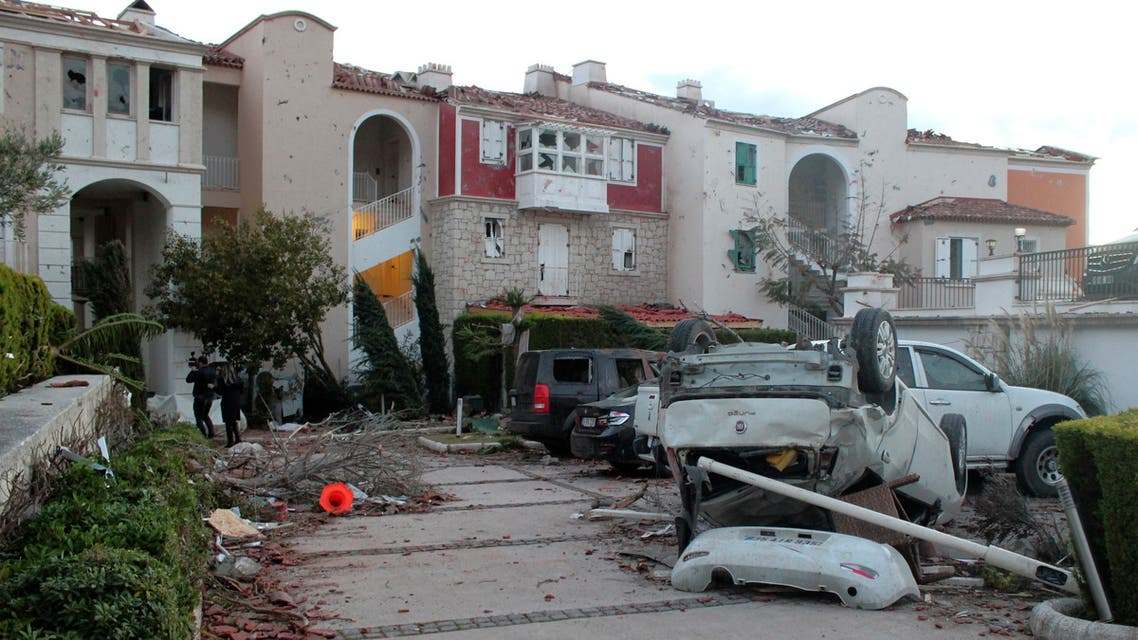 People walk among the debris after a small tornado has struck Cesme, a town on Turkey's Aegean coast, leaving a path of destruction and injuring sixteen people, Friday, Feb. 12, 2021. (AP)