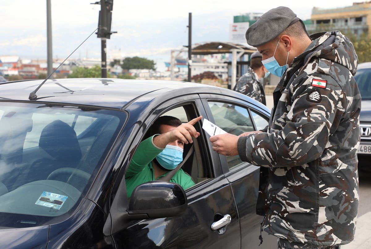 A police officer wearing a face mask talks with a driver at a checkpoint in Beirut, Jan. 15, 2021. (Reuters)