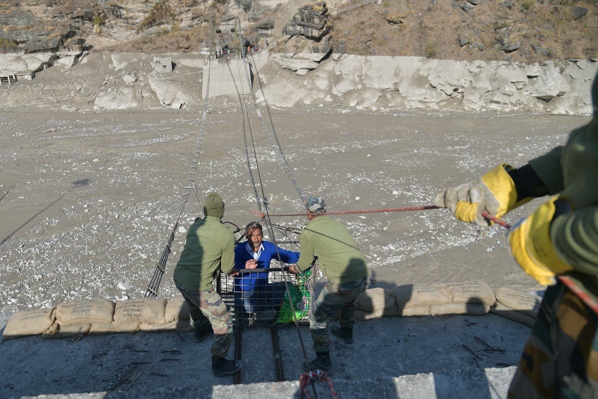 A resident is helped out of a metal basket by Indo-Tibetan Border Police personnel after crossing the Roshiganga river on a temporary zip-line in Chamoli district on February 12, 2021. (AFP)