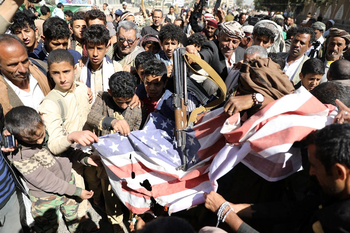 Houthi supporters shatter the US flag during a demonstration outside the US embassy against the decision to designate the Houthis a foreign terrorist organization, in Sanaa, Yemen Jan. 18, 2021. (Reuters)