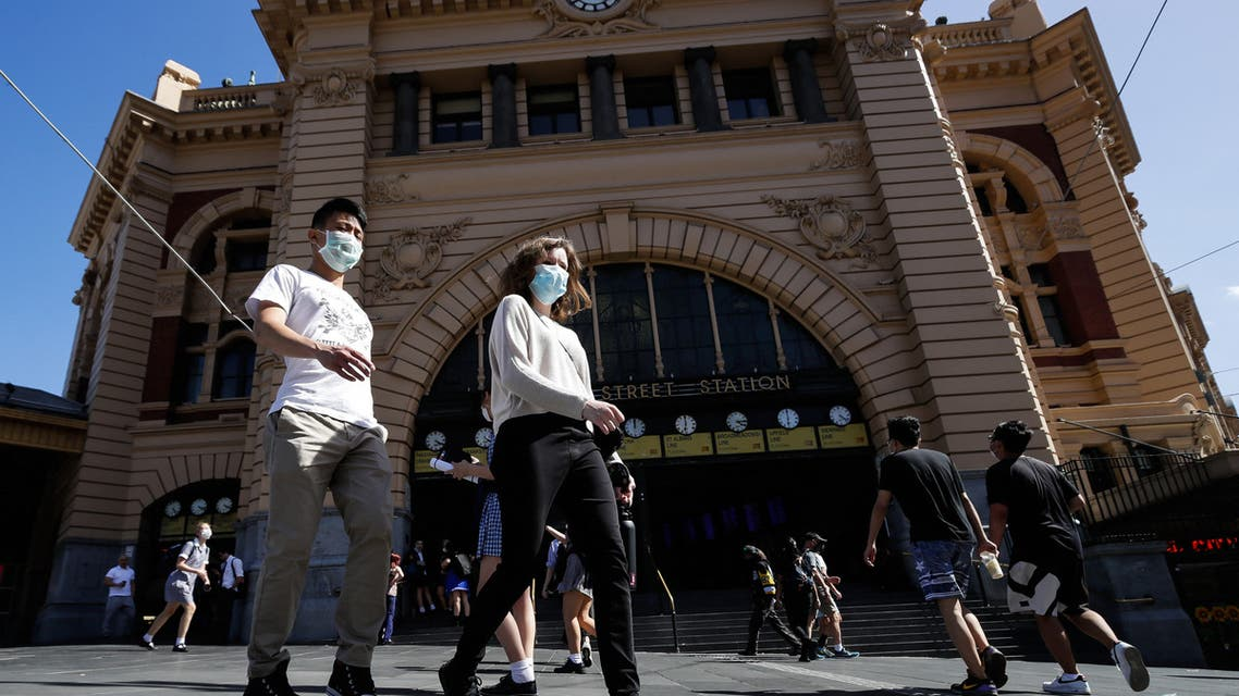 People cross a street in Melbourne on February 12, 2021, after authorities ordered a five-day state-wide lockdown starting at midnight local time to stamp out a new coronavirus outbreak. (AFP)