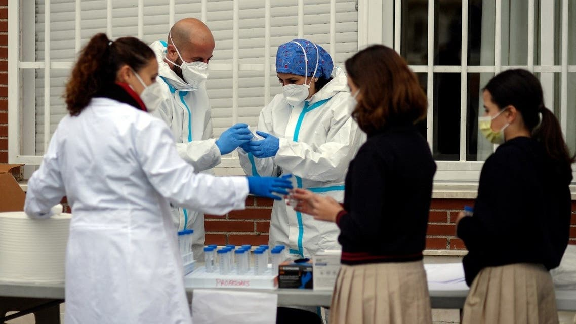 Medics collect saliva samples from pupils in a school in Madrid on December 17, 2020 for a study on coronavirus transmission between children and from children to adults. (Oscar del Pozo/AFP)