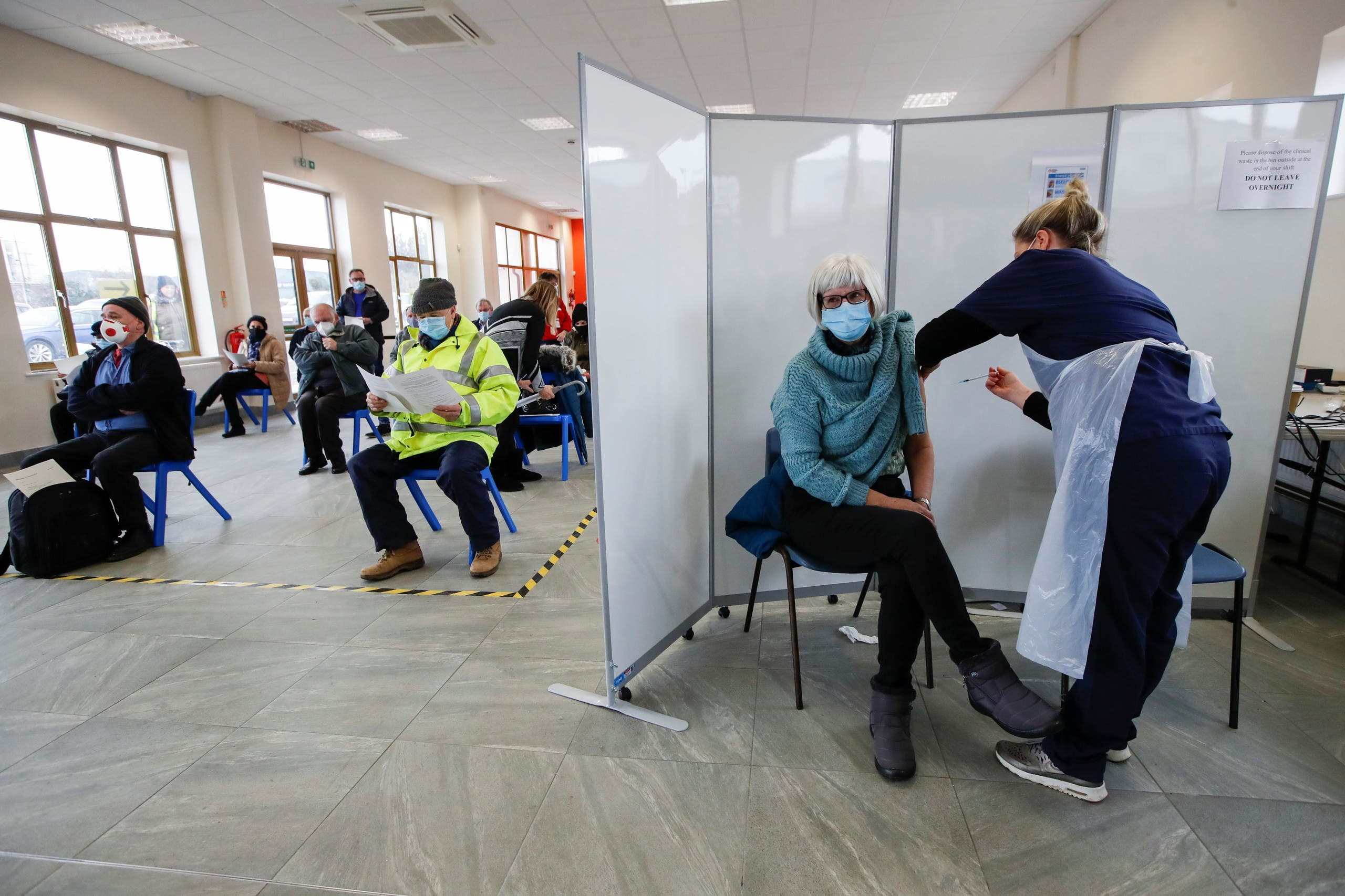 A woman receives a dose of a COVID-19 vaccine at the vaccination center at The Guru Nanak Temple, amid the coronavirus outbreak in Bedford, Britain, February 10, 2021. (Reuters/Paul Childs)