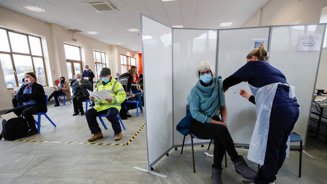 A woman receives a dose of a COVID-19 vaccine at the vaccination centre at The Guru Nanak Temple, amid the outbreak of coronavirus disease (COVID-19) in Bedford, Britain, February 10, 2021. REUTERS/Paul Childs