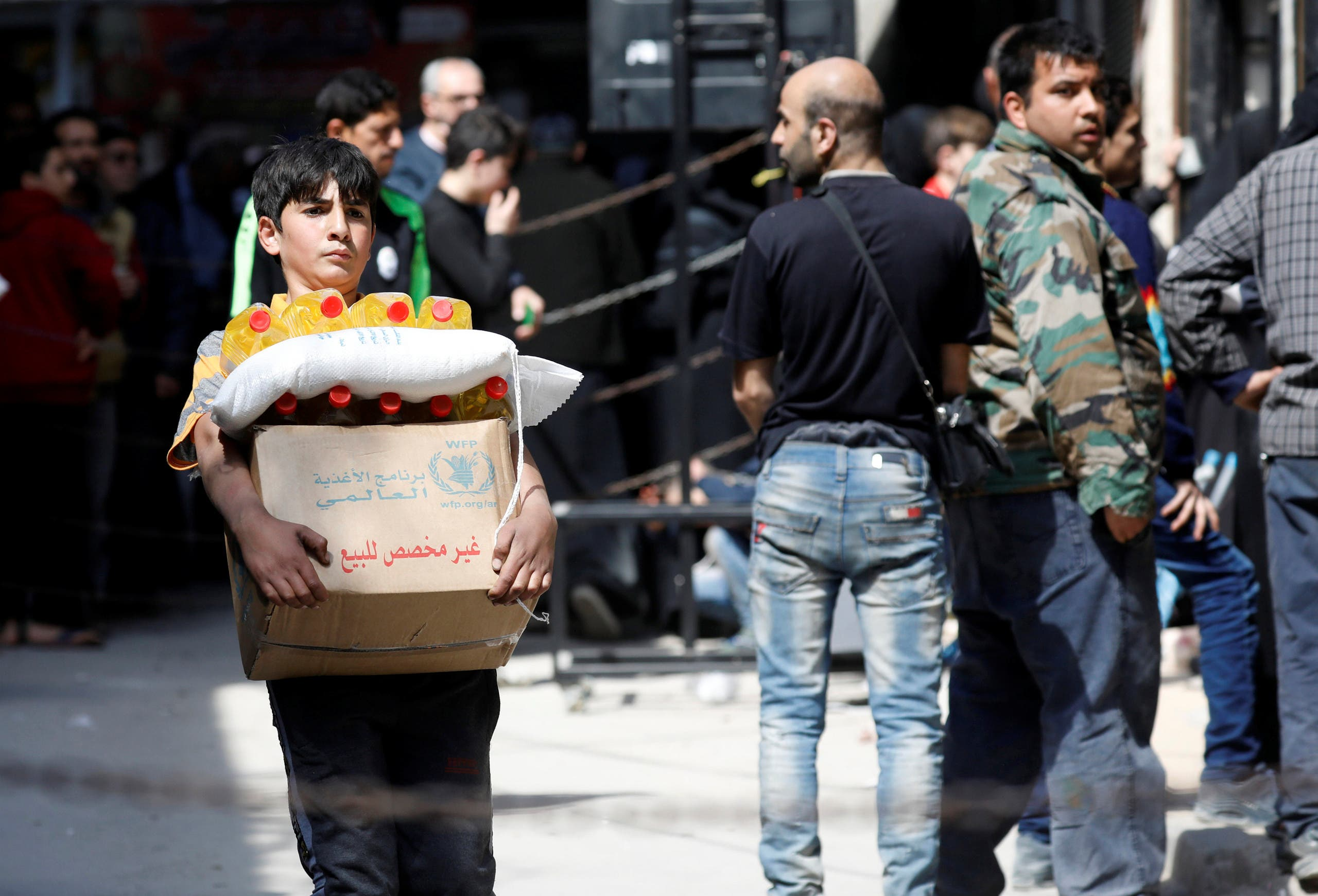 طفل سوري في حلب يحمل علبة مساعدات غذائية في ابريل 2019