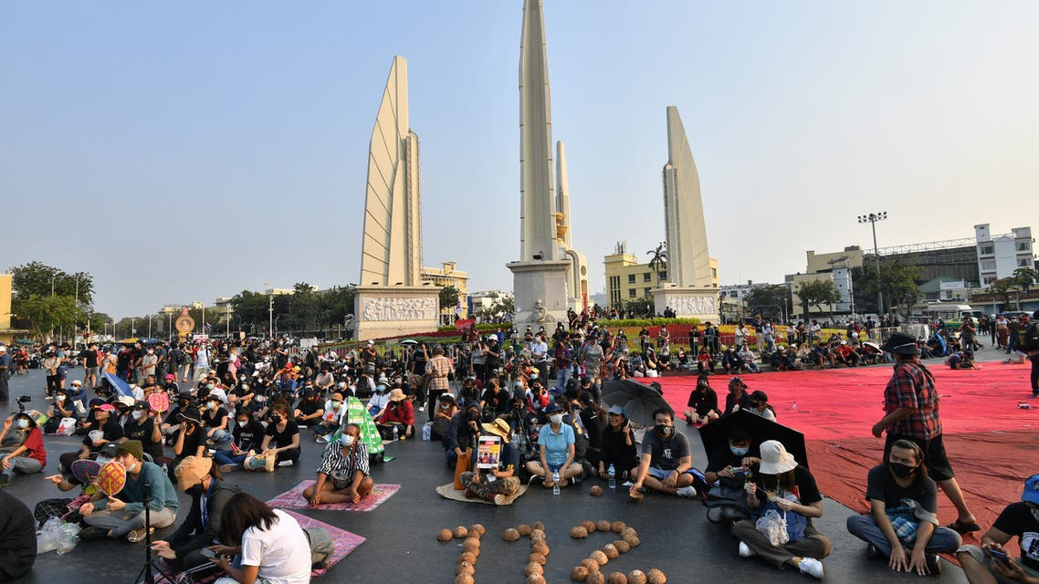 Pro-democracy protesters sit next to the numbers 112, signifying the Thai royal defamation law, spelled out with coconut shells as they take part in an anti-government rally near the Democracy Monument in Bangkok on February 13, 2021. (AFP)