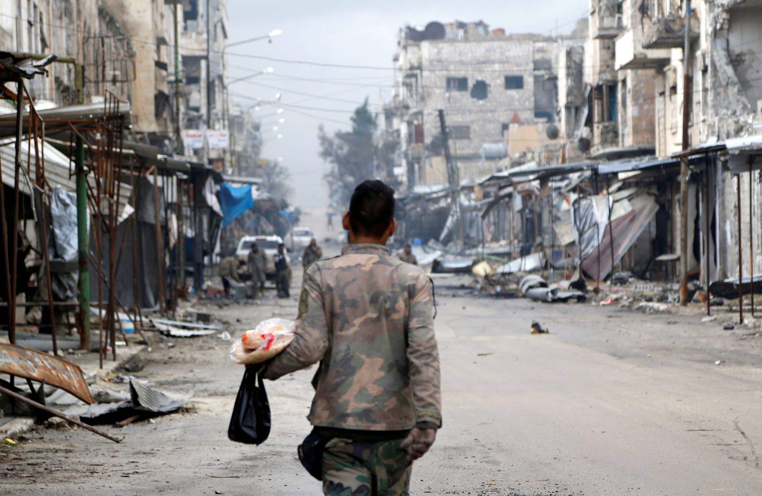 جندي في النظام السوري يمر في معرة النعمان المدمرة حاملاً مواد غذائية في يناير 2020