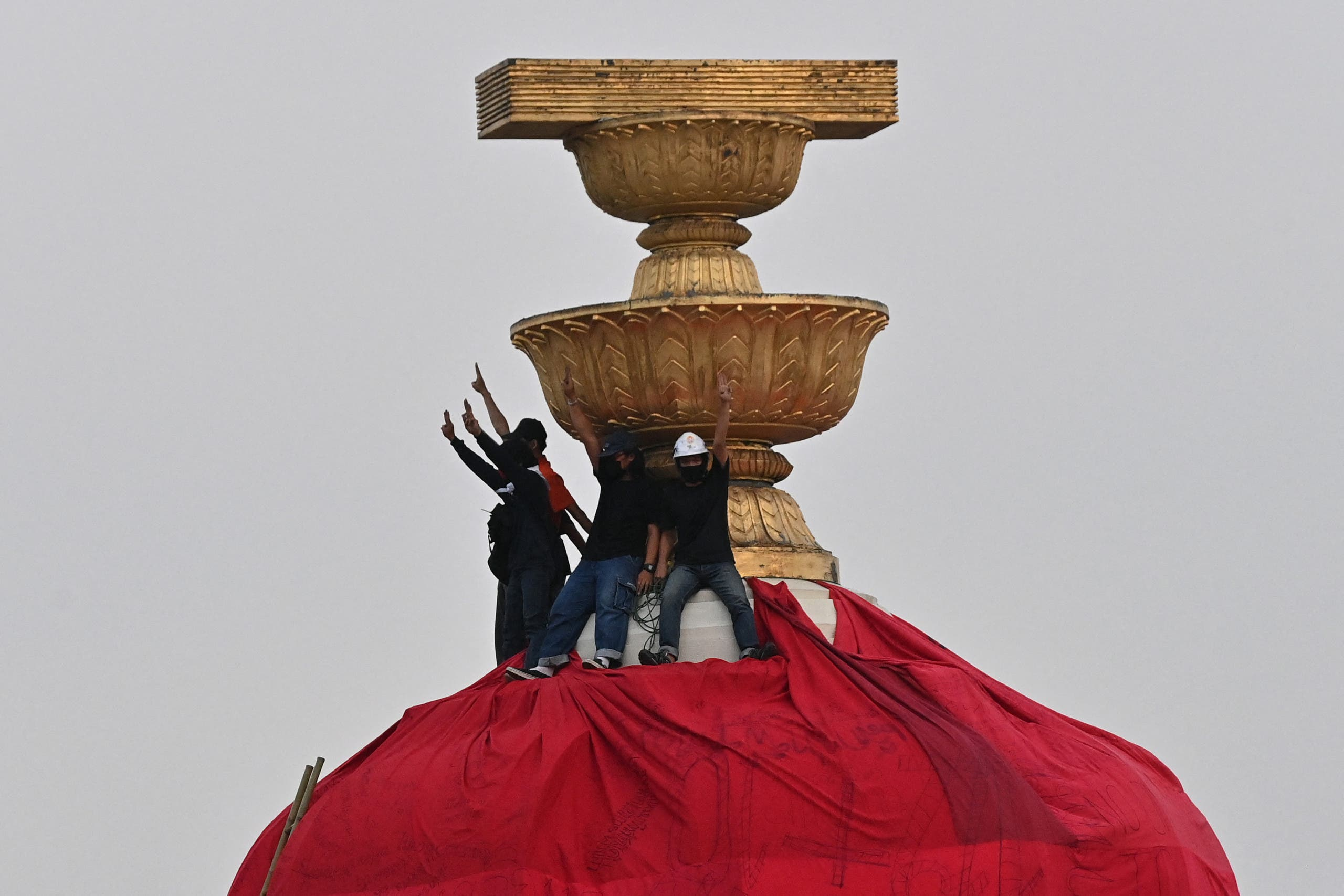 Protesters hold up the three finger salute as they wrap a part of the Democracy Monument with a large red sheet with pro-democracy messages written on it during an anti-government rally in Bangkok on February 13, 2021. (AFP)
