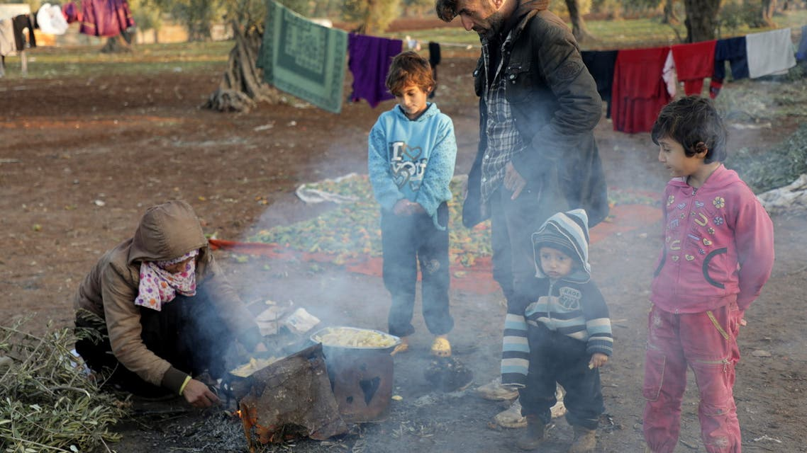 Internally displaced Syrians prepare food at a camp in the Northern Aleppo countryside, Syria December 20, 2020. Picture taken December 20, 2020. REUTERS/Mahmoud Hassano