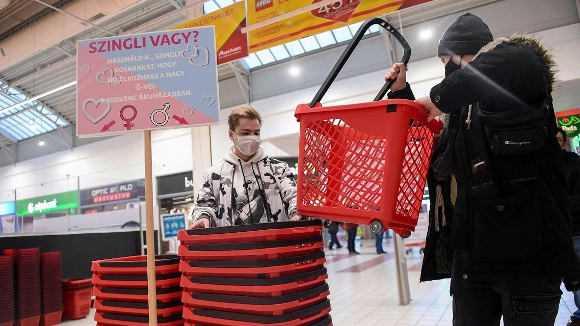 Two single young men pick up their signed plastic shopping baskets at a French Auchan supermarket in Csomor town, Hungary, on February 12, 2021, a few days ahead of Valentine's Day. (Attila Kisbenedek/AFP)