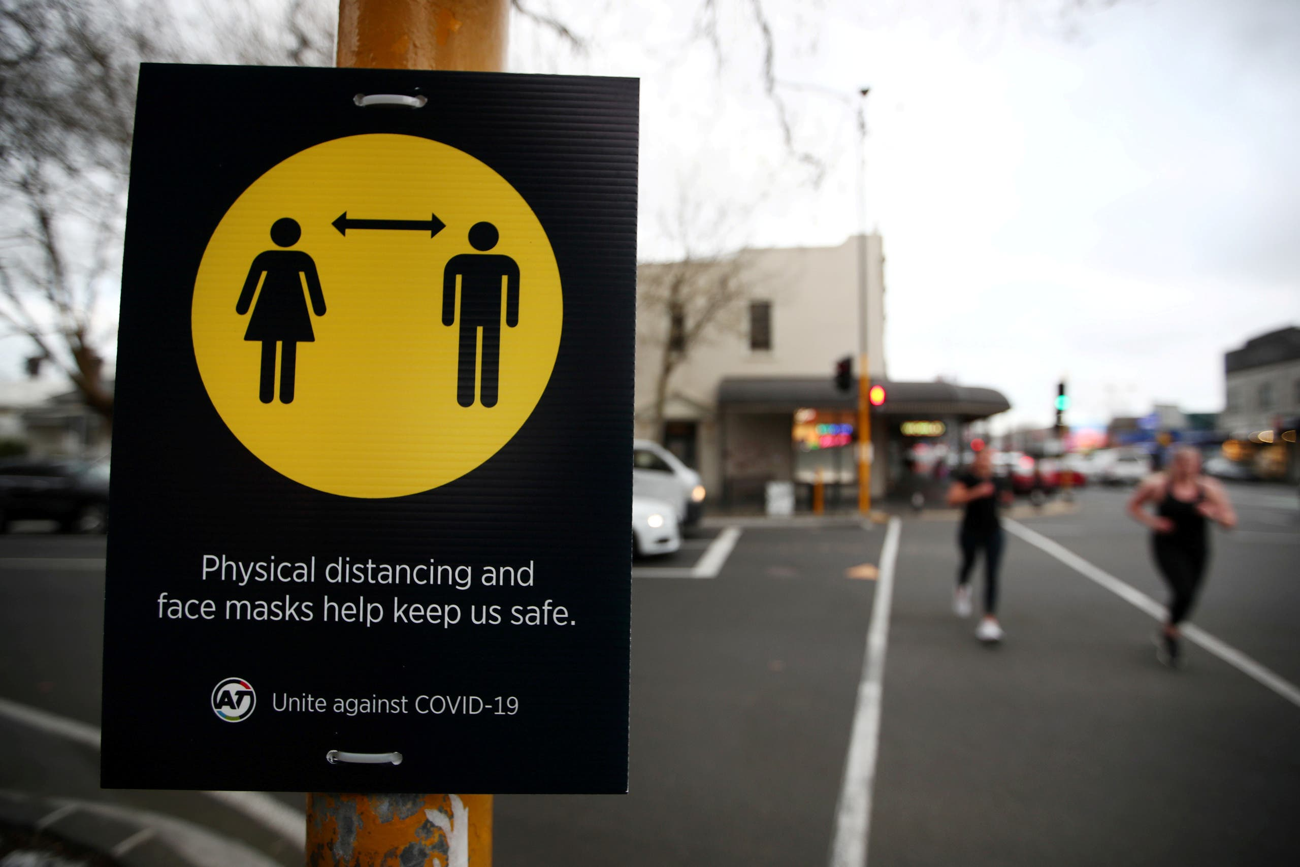 People jog past a social distancing sign on the first day of New Zealand's new coronavirus disease (COVID-19) safety measure that mandates wearing of a mask on public transport, in Auckland, New Zealand, August 31, 2020. (Reuters)