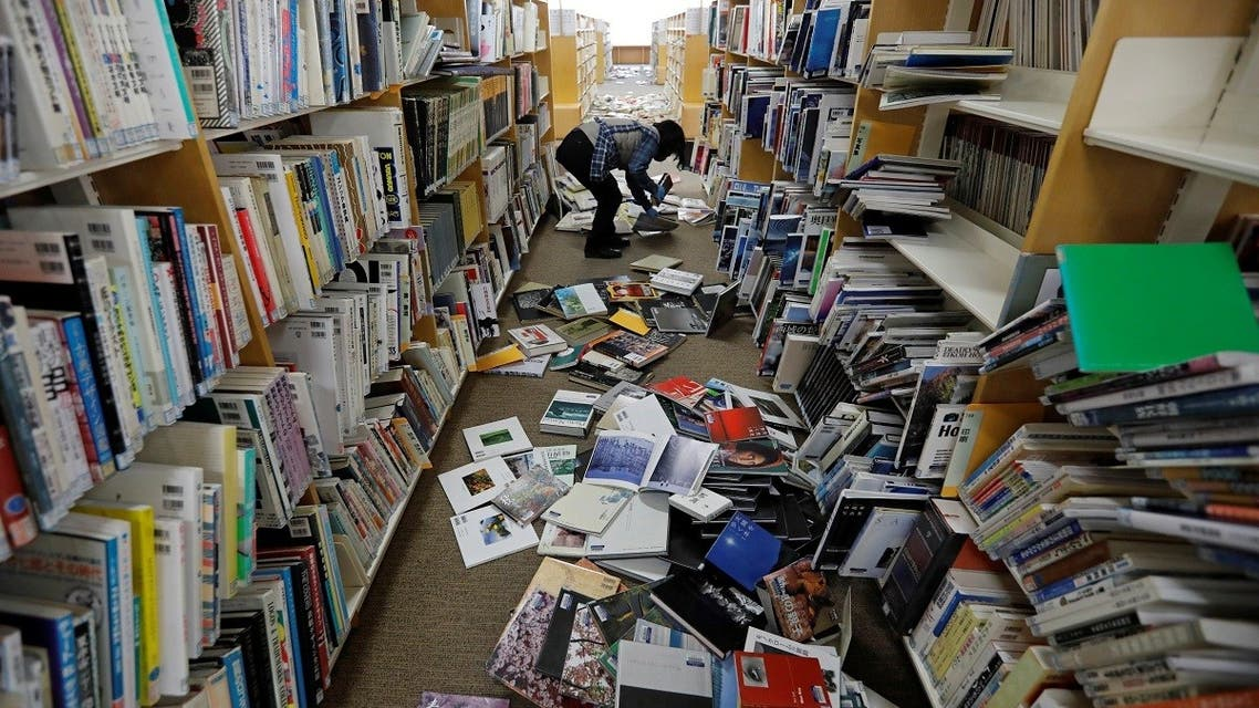 A staff member of library tries to restore books after they fell from book shelves by a strong earthquake at Iwaki City library in Iwaki, Fukushima prefecture, Japan February 14, 2021. (Reuters)