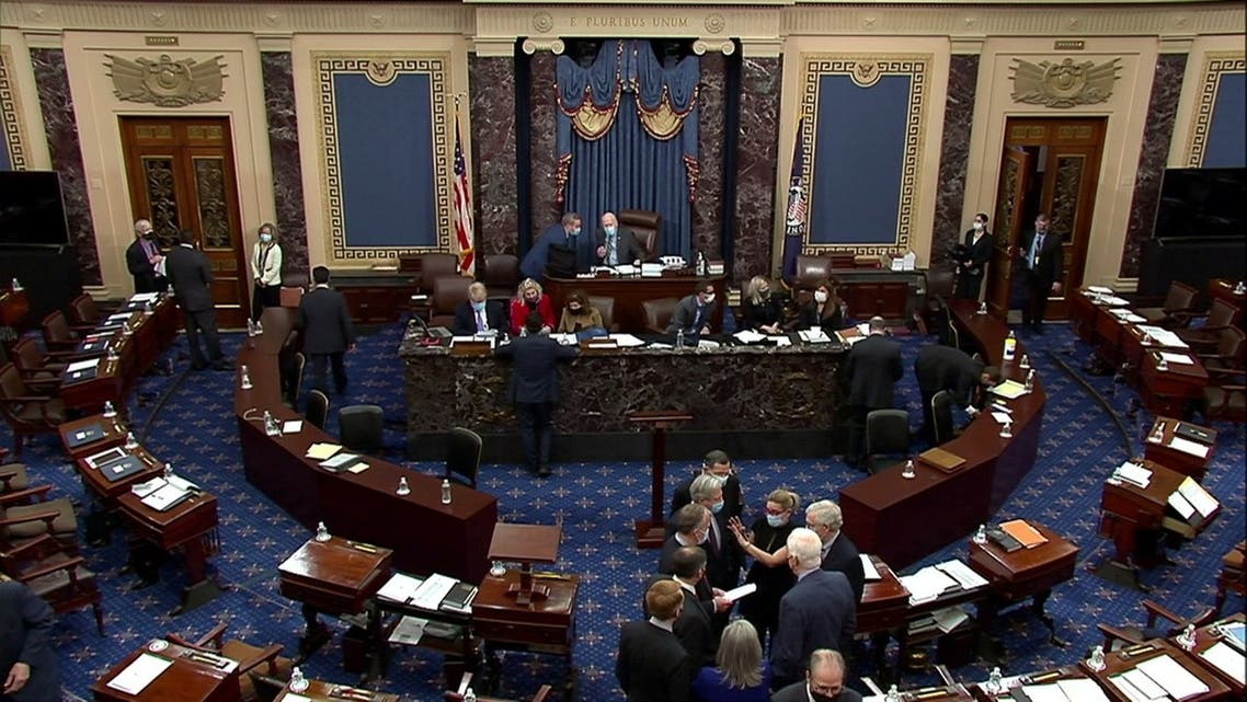 U.S. Senate Minority Leader Mitch McConnell (R-KY) huddles on the Senate floor with Senator Kyrsten Sinema (D-AZ), Senator John Barrasso (R-WY), Senator John Hoeven (R-ND), Senator Dan Sullivan (R-AK), Senator James Lankford (R-OK), Senator Joni Ernst (R-IA) and Senator John Cornyn (R-TX) and others after the Senate voted for witnesses during the fifth day of the impeachment trial of former president Donald Trump on charges of inciting the deadly attack on the U.S. Capitol, on Capitol Hill in Washington, U.S., February 13, 2021. U.S. Senate TV/Handout via Reuters EDITORIAL USE ONLY NO COMMERCIAL SALES
