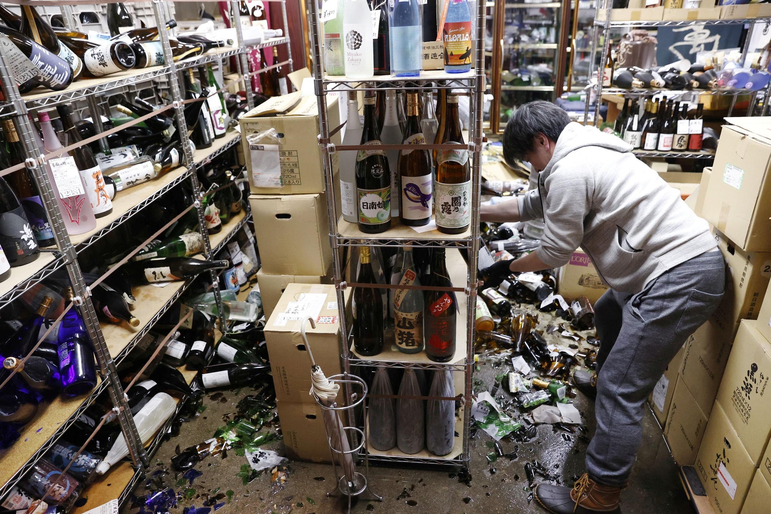 A worker cleans up broken bottles at a liquor shop after a strong quake in Fukushima, Japan, February 13, 2021, in this photo taken by Kyodo. (Kyodo/via Reuters)