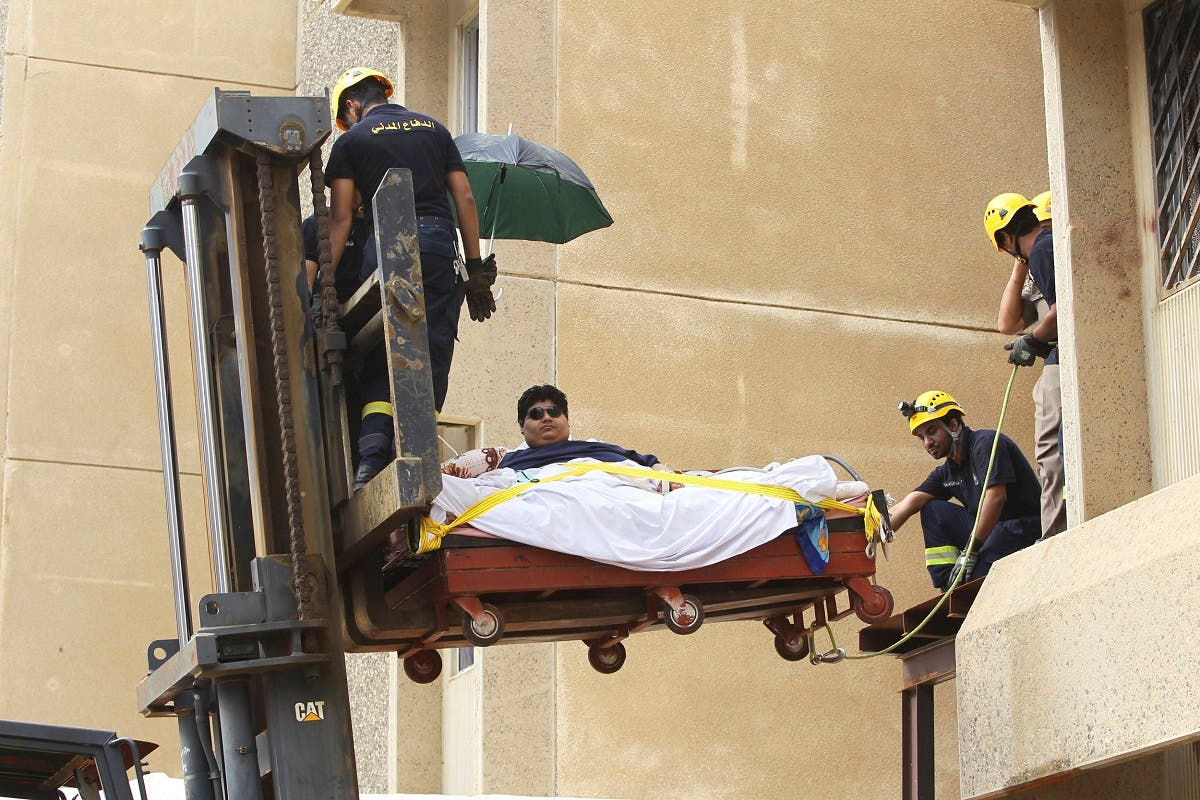 Saudi Civil Defence members use a forklift to move Khaled Mohsen Shaeri, 20, from his house in the Saudi city of Jizan, and to be airlifted to the capital Riyadh for medical treatment, August 19, 2013. (Reuters)