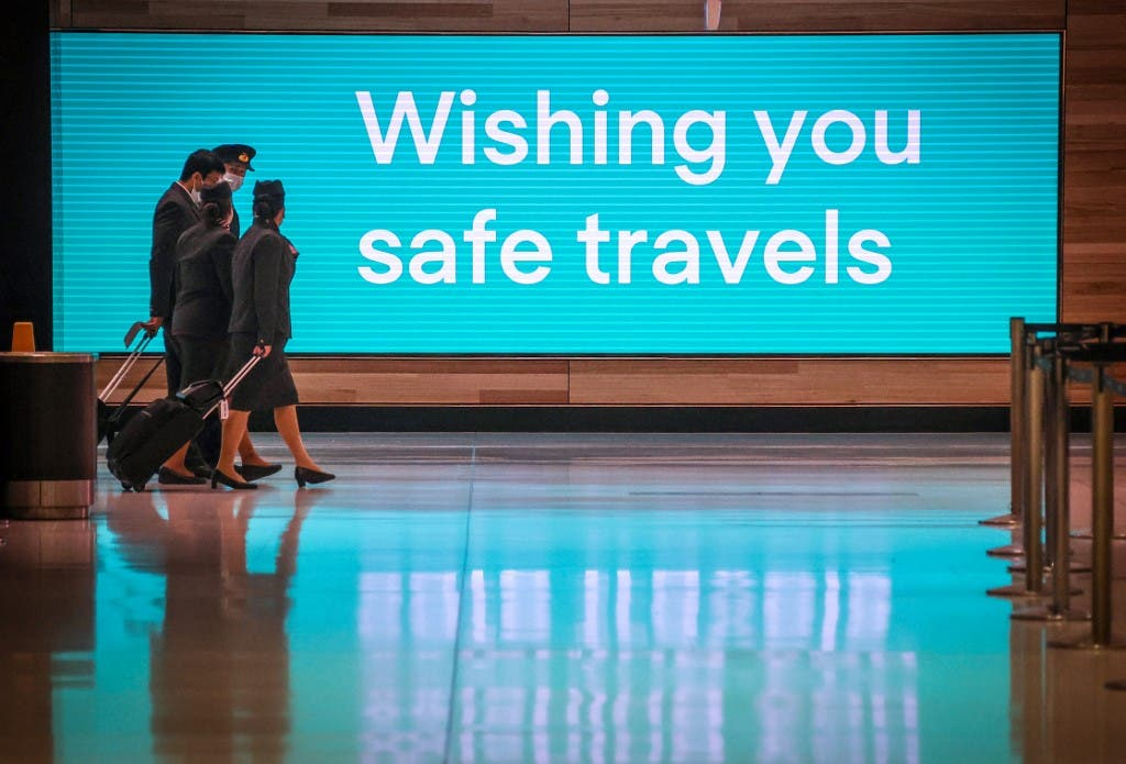 Flight crew members wearing face masks as a preventive measure against the COVID-19 novel coronavirus as they walk past an illuminated sign in the Sydney International Airport in Sydney. (File photo: AFP)
