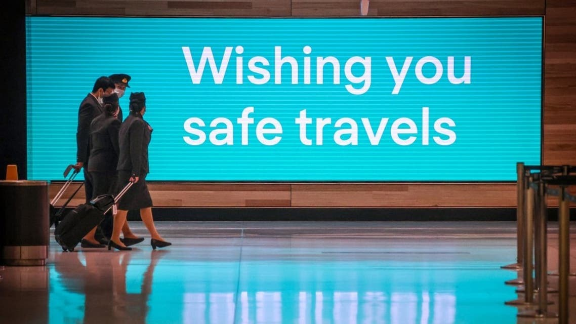 Flight crew members wearing face masks as a preventive measure against the COVID-19 novel coronavirus as they walk past an illuminated sign in the Sydney International Airport in Sydney. (AFP)