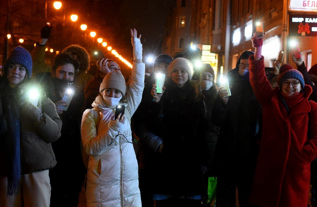 People turn on the flashlights of their mobile phones during Valentine Day's flashmobs in support of jailed opposition politician Alexei Navalny in Saint Petersburg on February 14, 2021. (AFP)