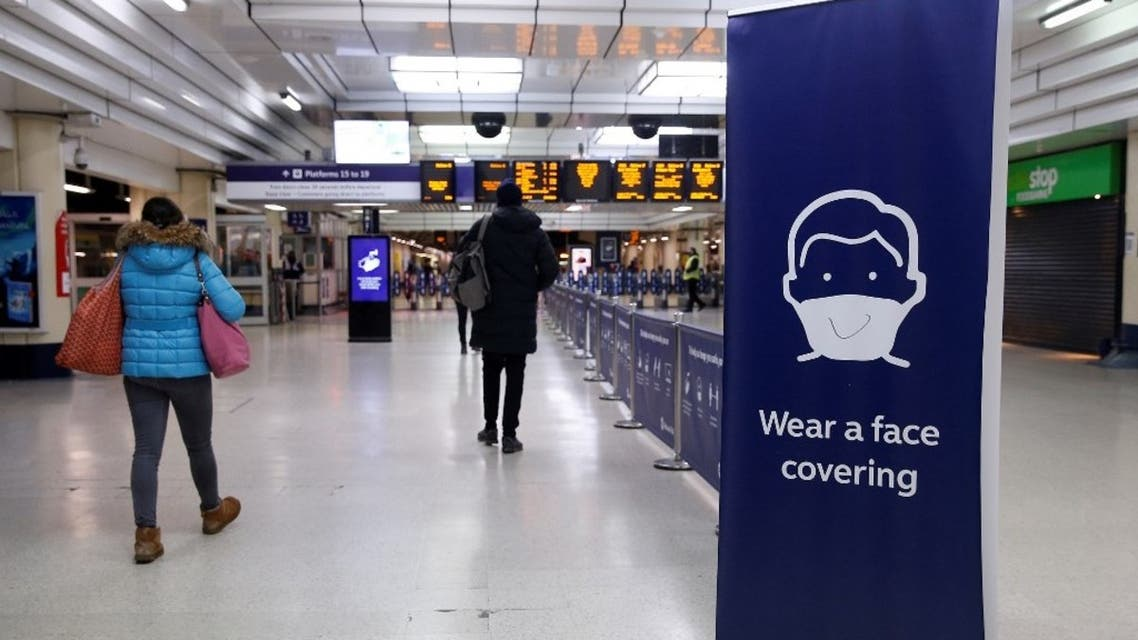 Travellers pass a Covid-19 information poster alerting them that the wearing of masks is compulsory, inside Victoria train station in central London on January 25, 2021. (AFP)