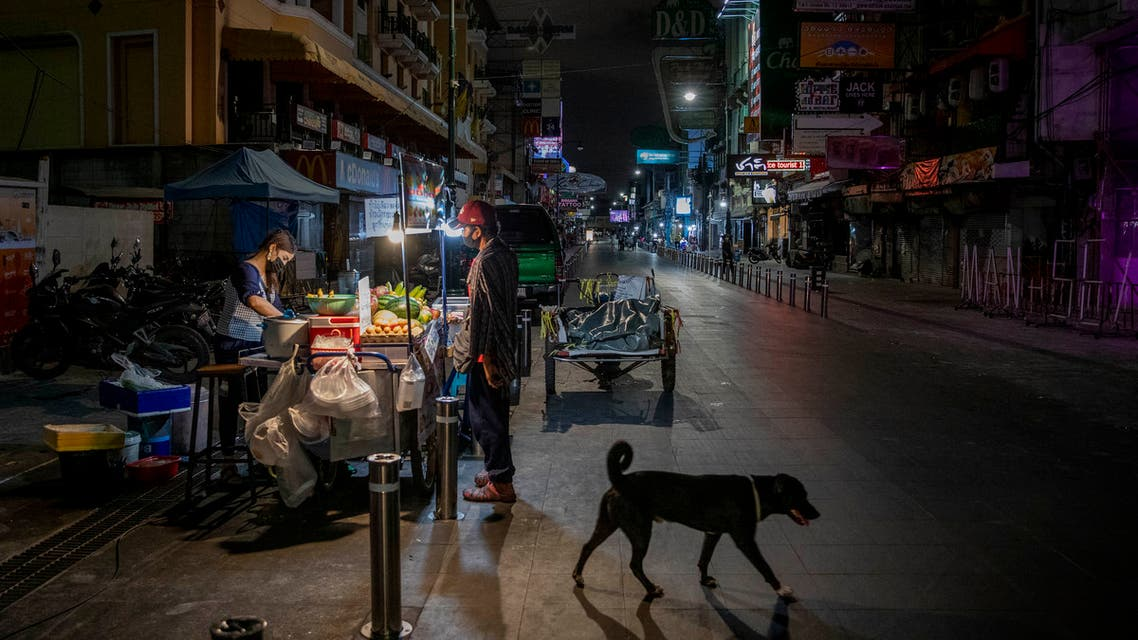 An alone street vender cooks a meal for a customer at Khao San road, a popular hangout with bars and entertainment for Thais and tourists in Bangkok, Thailand. (AP)