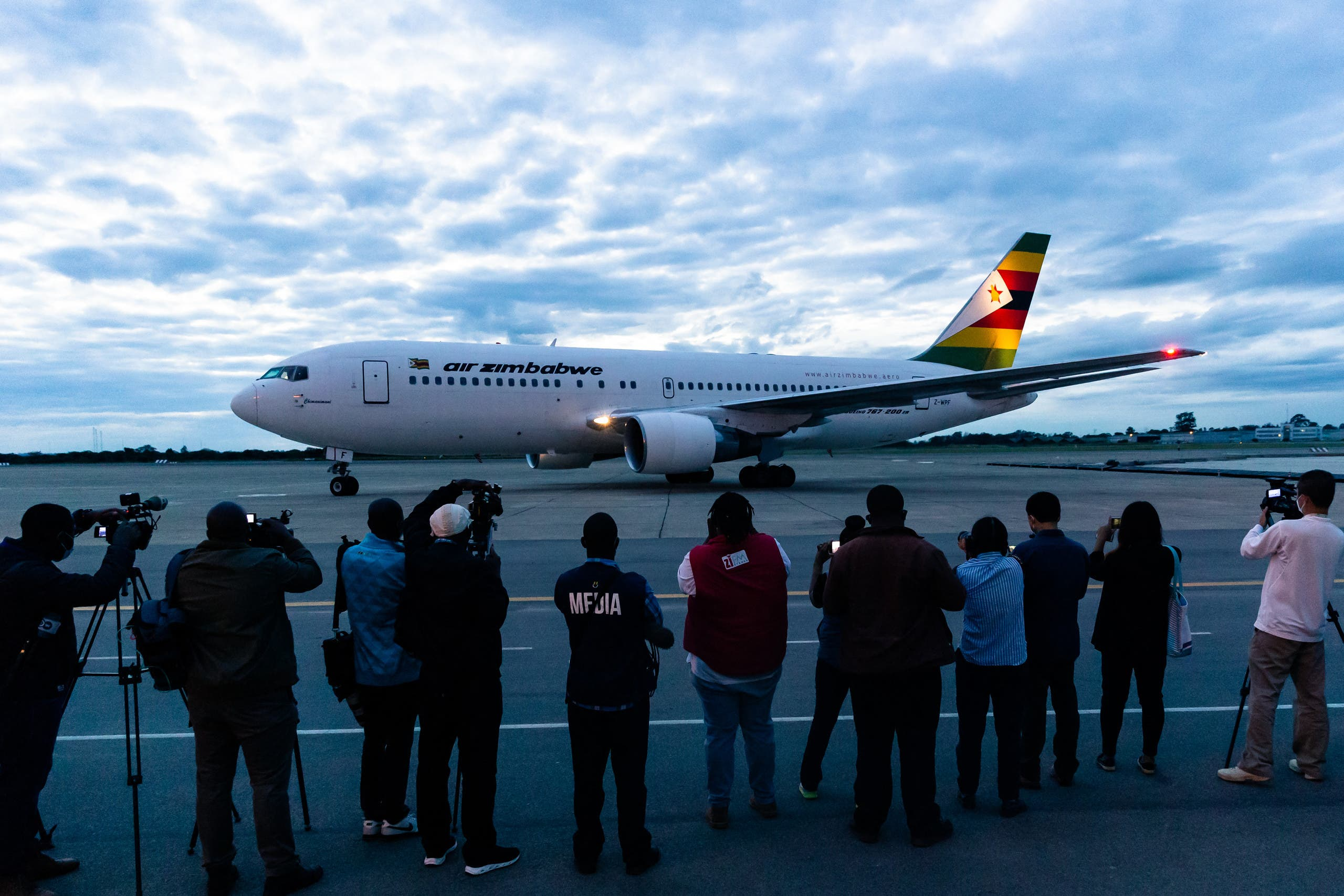 Journalists take footage as an Air Zimbabwe aeroplane arrives with a donation of 200,000 doses of the Sinopharm coronavirus vaccine from China on February 15, 2021 at the Robert Mugabe International Airport. (AFP)