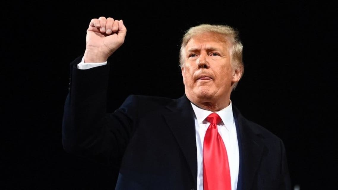 Donald Trump gestures holds up his fist after speaking during a rally to support Republican Senate candidates at Valdosta Regional Airport in Valdosta, Georgia on December 5, 2020. (AFP)
