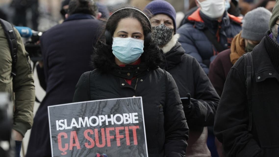 A woman holds a placard reading enough of islamophobia as protesters demonstrate against a bill dubbed as anti-separatism, in Paris on February 14, 2021. (AFP)