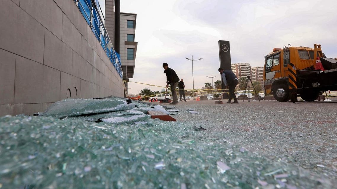 A worker cleans shattered glass on February 16, 2021 outside a damaged shop following a rocket attack the previous night in Arbil, the capital of the northern Iraqi Kurdish autonomous region. (Safin Hamed/AFP)