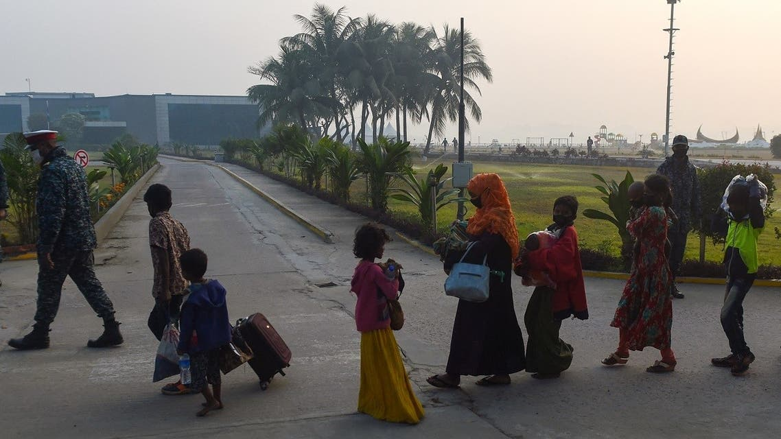Rohingya refugees walk with their belongings in Chittagong on January 30, 2021, as they make their way to a Bangladeshi navy ship that will take them to be relocated to Bhashan Char island in the Bay of Bengal. (AFP)
