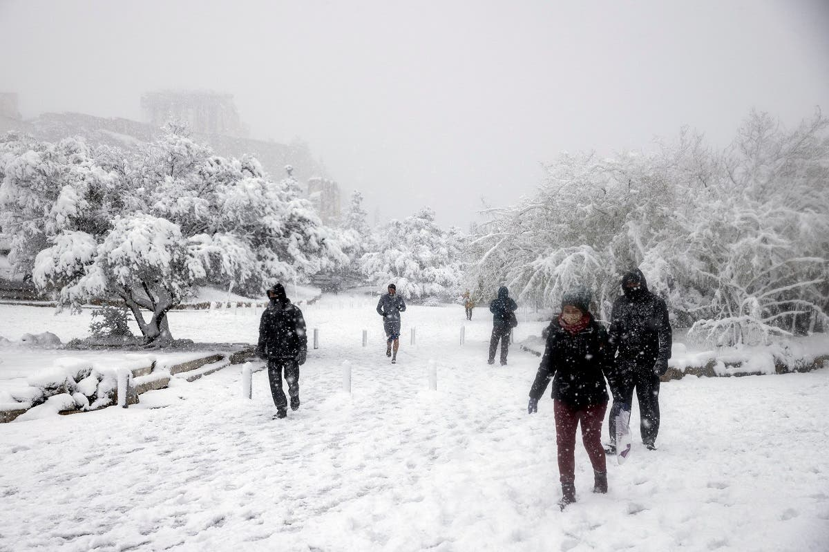 People make their way as the Parthenon temple is seen atop the Acropolis hill archaeological site during a heavy snowfall in Athens, Greece, on February 16, 2021. (Reuters)