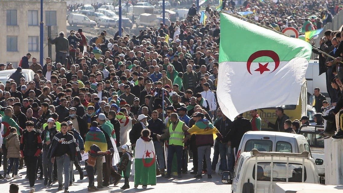Demonstrators carry national flags as they gather in the town of Kherrata, marking two years since the start of a mass protest movement there demanding political change, Algeria February 16, 2021. (Reuters/Ramzi Boudina)
