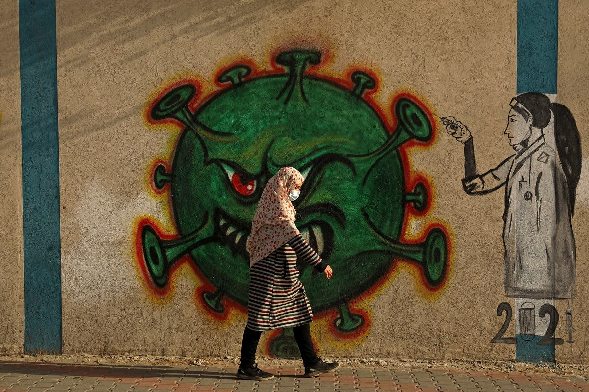 A Palestinian woman, wearing a protective mask amid the COVID-19 pandemic, walks past a coronavirus-inspired mural in Gaza City, on February 2, 2021. (File photo: AFP)