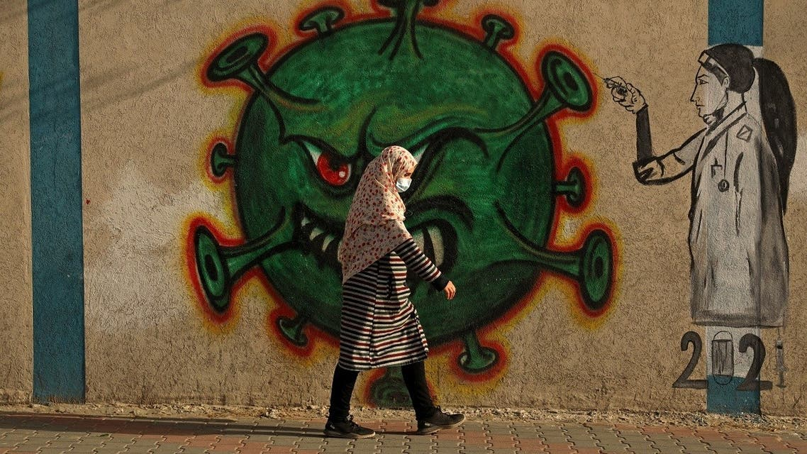 A Palestinian woman, wearing a protective mask amid the COVID-19 pandemic, walks past a coronavirus-inspired mural in Gaza City, on February 2, 2021. (Mohammed Abed/AFP)